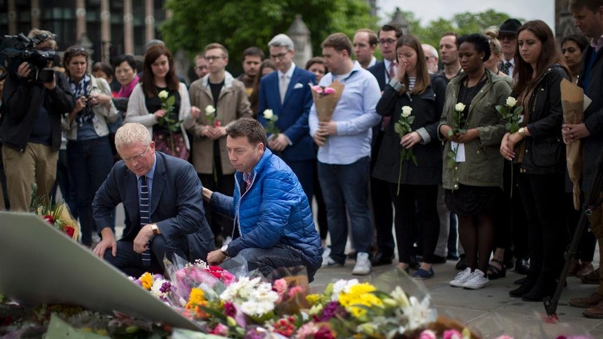 Staff from Britain's opposition Labour Party including at the front MP John Cryer, left, the Chair of the Parliamentary Labour Party and Iain McNicol, right, the party's General Secretary pay their respects after placing floral tributes for their colleague Jo Cox, the 41-year-old British Member of Parliament shot to death yesterday in northern England, on Parliament Square outside the House of Parliament in London, Friday, June 17, 2016. The married mother of two young children was shot to death Thursday afternoon in her constituency near Leeds, in northern England. Thomas Mair, 52, was arrested Thursday on suspicion of killing Cox, outside a library. (AP Photo/Matt Dunham)