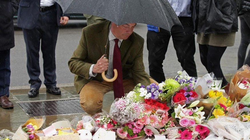 Leader of the UK Independence Party Nigel Farage lays a floral tribute for Jo Cox, the 41-year-old British Member of Parliament shot to death yesterday in northern England, on Parliament Square outside the House of Parliament in London, Friday, June 17, 2016. The mother of two young children was shot to death Thursday afternoon in her constituency near Leeds. A 52-year-old man has been arrested but has not been charged. (Yui Mok/PA via AP) UNITED KINGDOM OUT