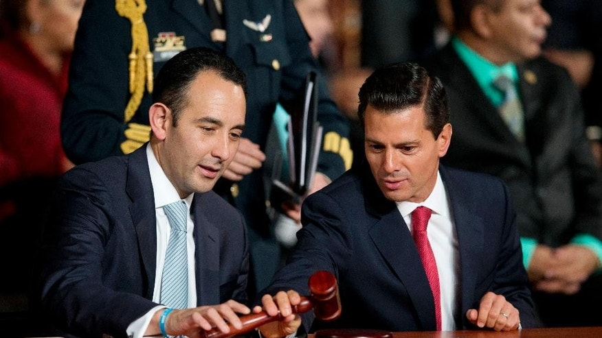 Senate President Roberto Gil Zuarth, left, and Mexican President Enrique Pena Nieto pick up a gavel just after it was used to inaugurate Mexico's new justice system, reforms that have been years in the making, in Mexico City, at the stroke of midnight on Saturday, June 18, 2016. Saturday is the deadline for implementing a new justice system based on open, oral trials. For Mexico, it is a remarkable change from a century-old judicial system of paper-shuffling court cases in which defendants rarely testified before the judge ruling on their fate from within a cramped, bureaucrat's office.(AP Photo/Rebecca Blackwell)