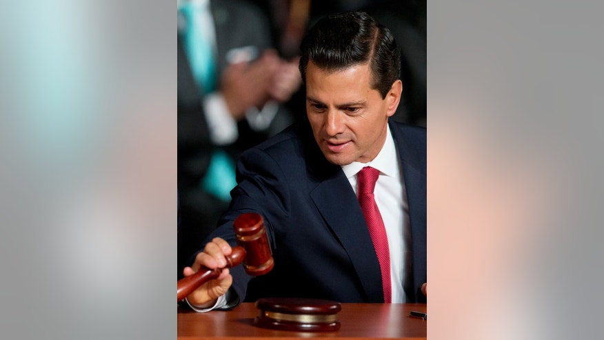 Mexican President Enrique Pena Nieto inspects a gavel just after it was used to inaugurate Mexico's new justice system, reforms that have been years in the making, in Mexico City, at the stroke of midnight on Saturday, June 18, 2016. Saturday is the deadline for implementing a new justice system based on open, oral trials. For Mexico, it is a remarkable change from a century-old judicial system of paper-shuffling court cases in which defendants rarely testified before the judge ruling on their fate from within a cramped, bureaucrat's office.(AP Photo/Rebecca Blackwell)