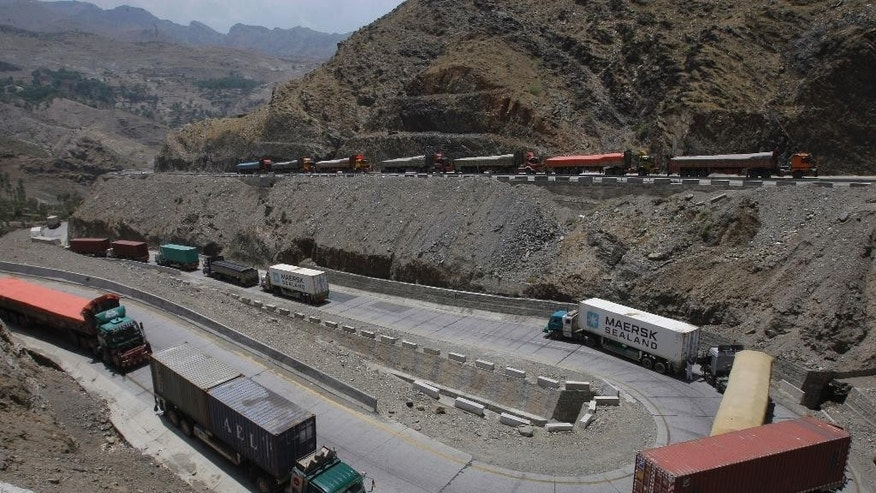 Afghanistan-bound trucks pass through a valley while moving toward the Torkham border crossing in Torkham, Pakistan, Saturday, June 18, 2016. Two security officials say Pakistan has reopened the Torkham border crossing with Afghanistan that was closed earlier this week following clashes between the two sides over Pakistan's construction of a gate to curb illegal cross-border movement. (AP Photo/Mohammad Sajjad)
