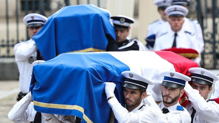 Police officers carry the coffins of the two police officials killed by an extremist claiming allegiance to IS, during a ceremony, Friday June 17, 2016 in Versailles, near Paris. Police commander Jean-Baptiste Salvaing and his companion, police administrator Jessica Schneider were stabbed Monday by attacker Larossi Abballa, who was killed in a police raid. (AP Photo/Kamil Zihnioglu)