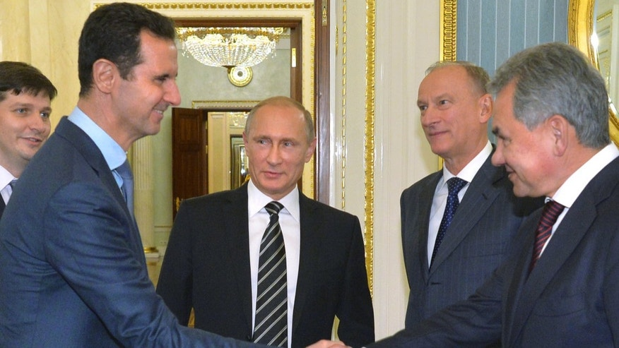 Assad, second left, shakes hand with Shoigu as Russian President Vladimir Putin, center, looks on, in October 2015.