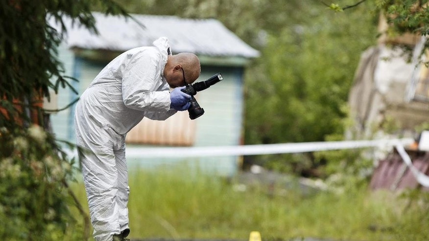 A police investigator takes photographs at the scene of a deadly shooting in Vihti, Finland Saturday, June 18, 2016. Authorities in Finland say a shooter has killed a police officer and seriously wounded another after they approached a remote countryside property where gunfire had been reported. (Roni Rekomaa/Lehtikuva via AP) FINLAND OUT