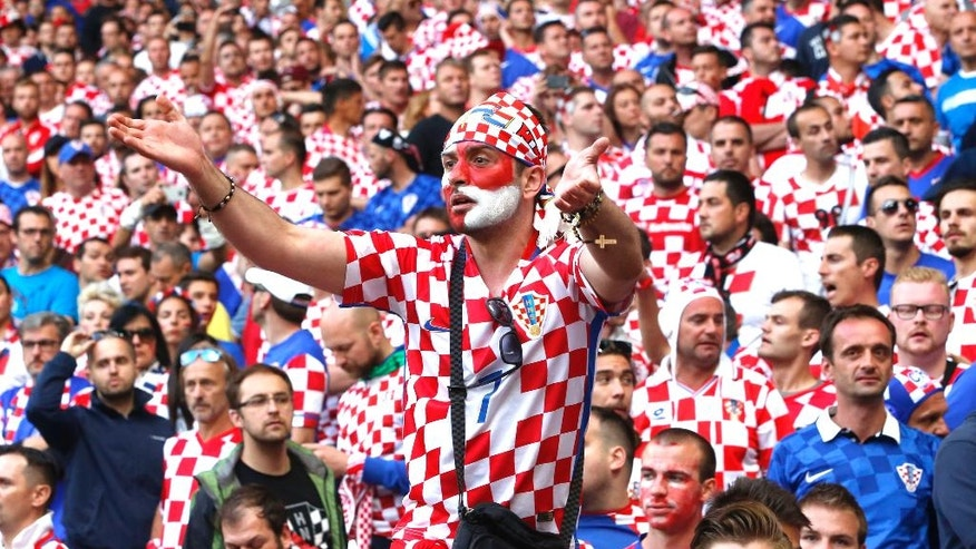 Croatian fans sit in the stands after flares were thrown on the pitch  during the Euro 2016 Group D soccer match between the Czech Republic and Croatia at the Geoffroy Guichard stadium in Saint-Etienne, France, Friday, June 17, 2016. (AP Photo/Darko Bandic)