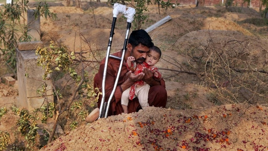 "Mohammed Tofeeq holds his 10-month-old daughter, Gulshan Tofeeq, while he prays at the grave of his wife Muqadas Tofeeq, who local police say was killed by her mother, in Butrawala village on the outskirts of Gujranwala, Pakistan, Saturday, June 18, 2016. Police have arrested the mother of Muqadas Tofeeq who is accused of killing her pregnant daughter for marrying against the wishes of her family. Violence against women is not uncommon in Pakistan where nearly 1,000 women are killed each year in so-called ""honor killings"" for violating conservative norms on love and marriage. (AP Photo/K.M. Chaudary)"