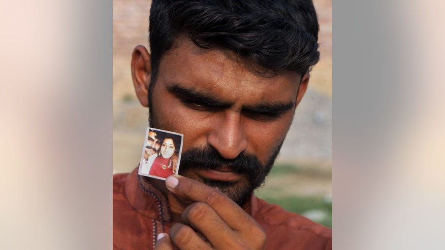 "Mohammed Tofeeq shows a picture of himself with his wife Muqadas Tofeeq, who local police say was killed by her mother, at his home in Butrawala village on the outskirts of Gujranwala, Pakistan, Saturday, June 18, 2016. Police in Pakistan say they have arrested the mother of Muqadas Tofeeq who is accused of killing her pregnant daughter for marrying against the wishes of her family. Violence against women is not uncommon in Pakistan where nearly 1,000 women are killed each year in so-called ""honor killings"" for violating conservative norms on love and marriage. (AP Photo/K.M. Chaudary)"