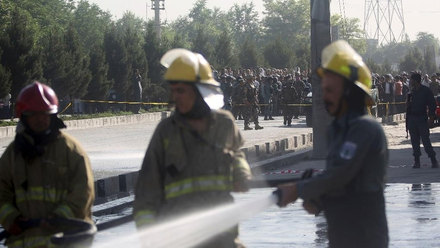 Afghan fire department clean a street as people watch at the site of a suicide attack in Kabul, Afghanistan, Monday, June 20, 2016. About a dozen people were killed Monday when a Taliban suicide bomber targeted their minibus in the Afghan capital, a government official said. (AP Photos/Massoud Hossaini)