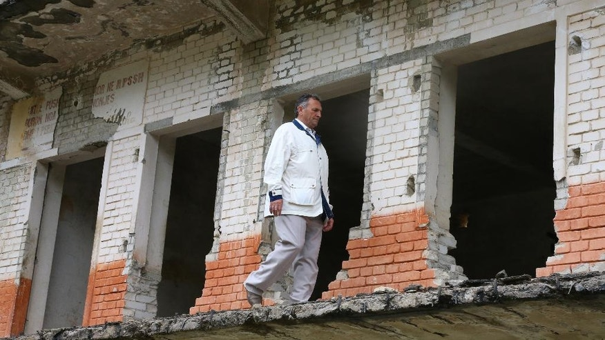 In this Saturday, May 21, 2016 photo, Zenel Drangu, a former political prisoner, walks past an abandoned building at the notorious labor camp of Spac northern Albania. As the prison falls into ruin, some of the former prisoners fear that the thousands who suffered there will be forgotten, and they are campaigning to have the site turned into a museum and to have May 21 declared a national day of remembrance for those who suffered under communism. (AP Photo/Hektor Pustina)