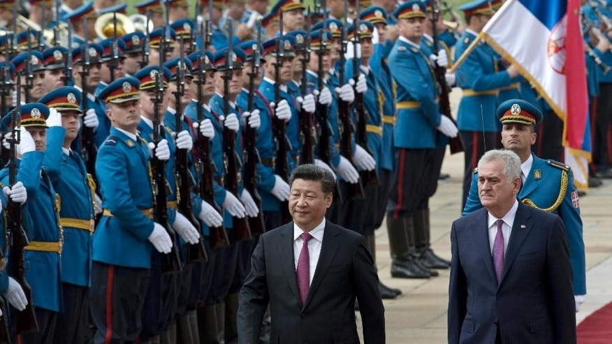 Chinese President Xi Jinping, center, and his Serbian counterpart, Tomislav Nikolic, right, walk past Serbian army Honor Guards during a welcoming ceremony in Belgrade, Serbia, Saturday, June 18, 2016. Xi arrived in Serbia for a visit meant to boost relations with the friendly nation and assert China's intention to increase its presence in the Balkans and Europe. (AP Photo/Marko Drobnjakovic)