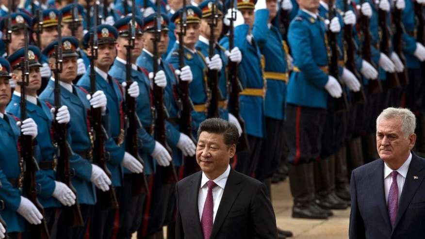 Chinese President Xi Jinping, center, and his Serbian counterpart, Tomislav Nikolic, walk past Serbian army Honor Guards in Belgrade, Serbia, Saturday, June 18, 2016. Xi arrived in Serbia for a visit meant to boost relations with the friendly nation and assert China's intention to increase its presence in the Balkans and Europe. (AP Photo/Marko Drobnjakovic)