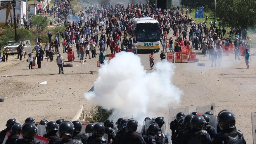 Riot police battle with protesting teachers who were blocking a federal highway in the state of Oaxaca, near the town of Nochixtlan, Mexico, Sunday, June 19, 2016. The teachers are protesting against plans to overhaul the country's education system which include federally mandated teacher evaluations.(AP Photo/Luis Alberto Cruz Hernandez)