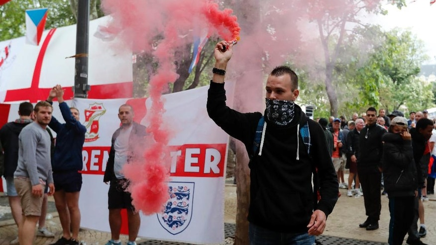 A man holds a flare moments before it was taken away from him by England supporters in Saint-Etienne, France, Sunday, June 19, 2016, one day ahead of the Euro 2016 Group B soccer match against Slovakia. (AP Photo/Darko Bandic)