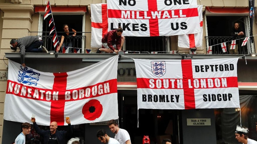 England supporters put up flags in downtown Saint-Etienne, France, Sunday, June 19, 2016, one day ahead of the Euro 2016 Group B soccer match against Slovakia. (AP Photo/Darko Bandic)