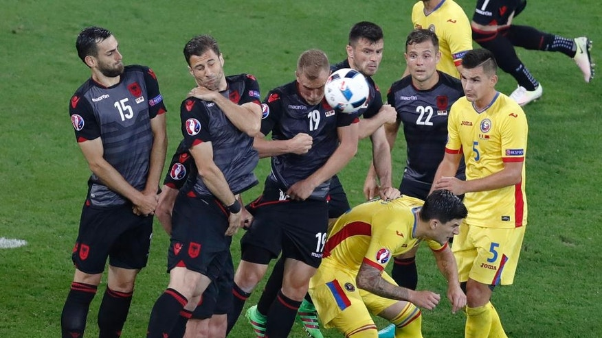 Albania's Bekim Balaj, third from left, deflects a free kick during the Euro 2016 Group A soccer match between Romania and Albania at the Grand Stade in Decines-Charpieu, near Lyon, France, Sunday, June 19, 2016. (AP Photo/Michael Sohn)