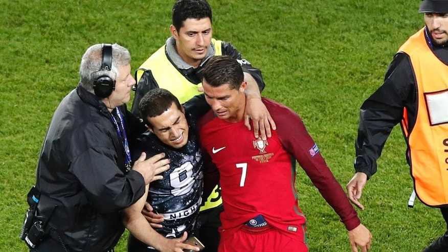 A man who invaded the pitch reacts next to Portugal's Cristiano Ronaldo at the end of the Euro 2016 Group F soccer match between Portugal and Austria at the Parc des Princes stadium in Paris, France, Saturday, June 18, 2016.. (AP Photo/Francois Mori)