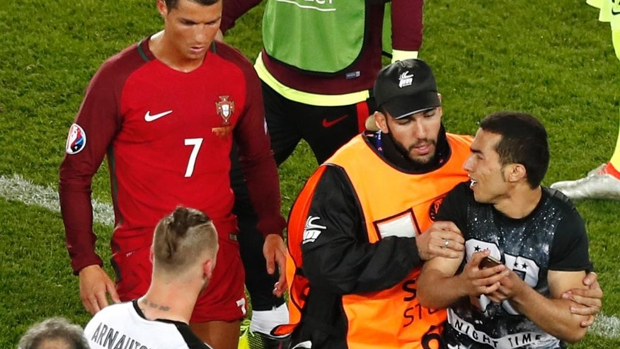 Portugal's Cristiano Ronaldo walks as a steward tries to block a man who invaded the pitch asking to take a selfie with him at the end of the Euro 2016 Group F soccer match between Portugal and Austria at the Parc des Princes stadium in Paris, France, Saturday, June 18, 2016. (AP Photo/Francois Mori)