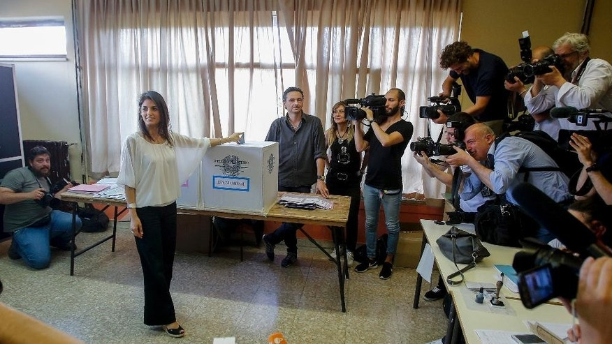 Anti-establishment 5-Star Movement (M5S) candidate as Rome's mayor Virginia Raggi poses for photographers as she casts her ballot in polling station in Rome, Sunday, June 19, 2016. Mayoral runoffs are held in Rome, Milan and other big Italian cities Sunday. If Raggi wins, she'll be the first woman to serve as Rome mayor. (AP Photo/Fabio Frustaci)