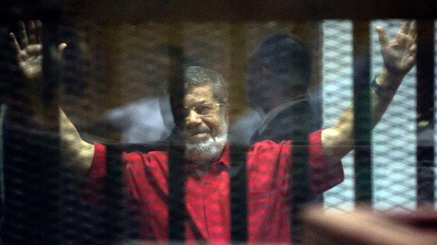 Former Egyptian President Mohammed Morsi, wearing a red jumpsuit that designates he has been sentenced to death, raises his hands inside a defendants cage in a makeshift courtroom at the national police academy, in an eastern suburb of Cairo, Egypt, Saturday, June 18, 2016. An Egyptian court has sentenced six people, including two Al-Jazeera employees, to death for allegedly passing documents related to national security to Qatar and the Doha-based TV network during the rule of Islamist president Mohammed Morsi. Morsi, the case's top defendant, was also sentenced on Saturday to 25 years in prison. He was ousted by the military in July 2013, and has already been sentenced to death in other cases. (AP Photo/Amr Nabil)