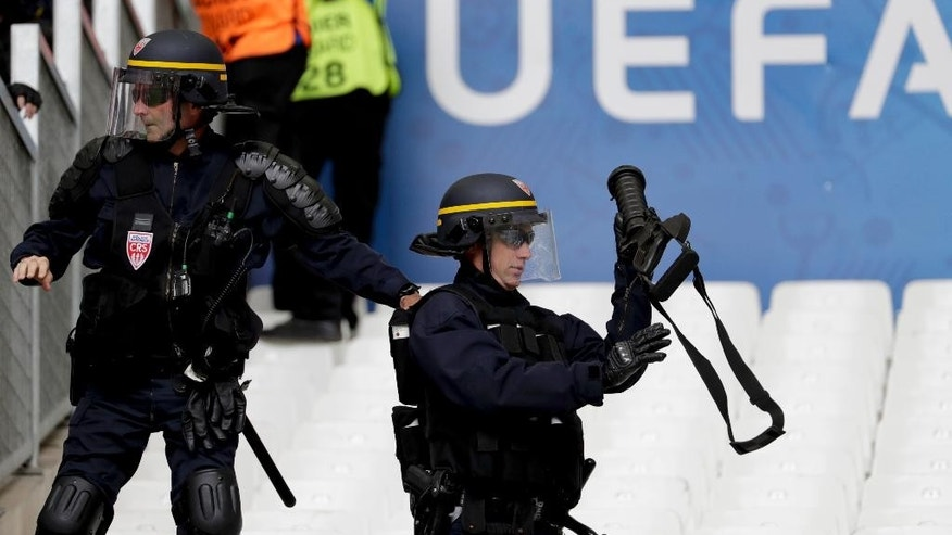 A French riot police officer adjusts his tear gas launcher prior to the Euro 2016 Group F soccer match between Iceland and Hungary at the Velodrome stadium in Marseille, France, Saturday, June 18, 2016. Hungarian fans have clashed with stewards ahead of their team's game against Iceland at the European Championship. (AP Photo/Ariel Schalit)