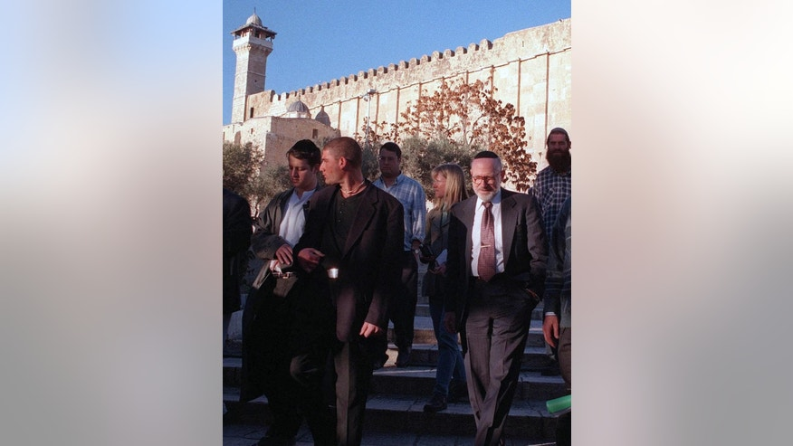 FILE -- In this Jan. 12, 1999 file photo, Miami-based millionaire Irving Moskowitz, right, leaves the Tomb of the Patriarchs during a tour of the Jewish enclave in the West Bank city of Hebron. Moskowitz an American philanthropist and patron of controversial ultra-nationalist Israeli settlers died and was buried Monday, June 20, 2016 at a cemetery in the Mount of Olives, within view of a Jewish enclave he helped establish in east Jerusalem. (AP PHOTO/Nasser Shiyoukhi, File)