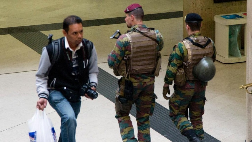 Two Belgian soldiers patrol at Brussels Central train station in Brussels on Sunday, June 19, 2016. The Belgian security level stays at level 3 after the Belgian federal prosecutor's office said early Saturday that homes and car ports were searched in 16 municipalities, mostly in and around Brussels in an anti-terror sweep. (AP Photo/Virginia Mayo)