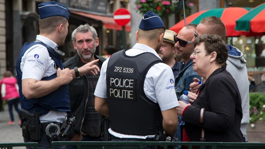 Belgian police help a group of tourists as they patrol in the historic Grand Place in Brussels on Sunday, June 19, 2016. The Belgian security level stays at level 3 after the Belgian federal prosecutor's office said early Saturday that homes and car ports were searched in 16 municipalities, mostly in and around Brussels in an anti-terror sweep. (AP Photo/Virginia Mayo)
