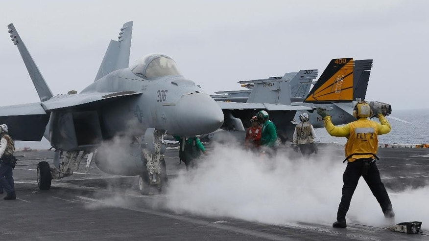 FILE - In this file photo from Wednesday, June 15, 2016, a flight deck director signals a fighter jet to move on the deck of the nuclear-powered aircraft carrier the USS John C. Stennis during joint military exercise between the United States, Japan and India off the coast 180 miles east of Japan's southernmost island of Okinawa. The U.S. says at least one Chinese ship tailed the USS John C. Stennis daily during its recent cruise through the South China Sea, although no hostile incidents were reported. (AP Photo/Shizuo Kambayashi, File)
