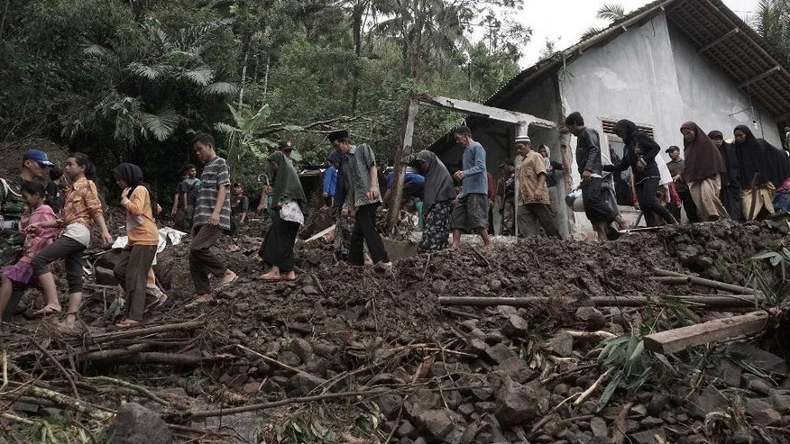 Villagers walk through the area affected by landslides in Banjarnegara, Central Java, Indonesia. Sunday, June 19, 2016. An Indonesian official said dozens of people have been killed by flooding and landslides in central Java and many others remain missing. (AP Photo)