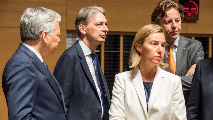 From left, Belgian Foreign Minister Didier Reynders, British Foreign Minister Philip Hammond, European Union High Representative Federica Mogherini and Dutch Foreign Minister Bert Koenders wait for the start of a meeting of EU foreign ministers at the EU Council building in Luxembourg, on Monday, June 20, 2016. EU foreign ministers meet Monday to discuss, among other issues, the situation in Libya. (AP Photo/Charles Caratini)