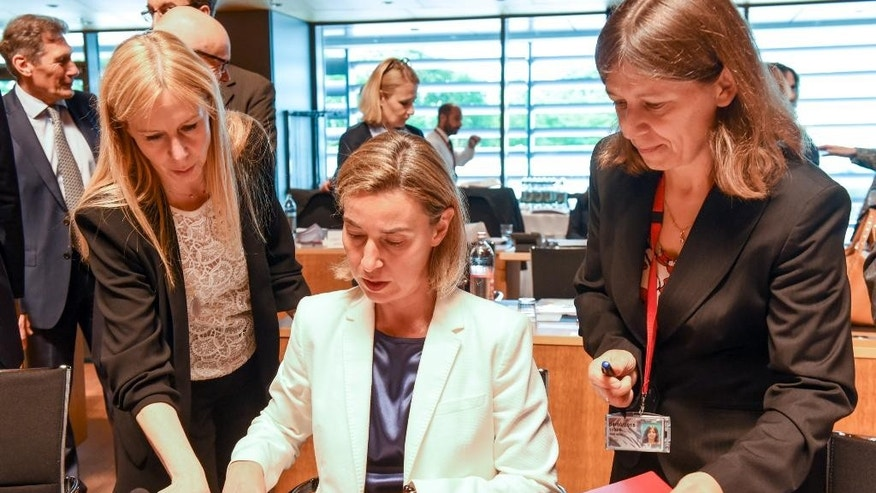 European Union High Representative Federica Mogherini, center, signs papers ahead of a meeting of EU foreign ministers at the EU Council building in Luxembourg, on Monday, June 20, 2016. EU foreign ministers meet Monday to discuss, among other issues, the situation in Libya. (AP Photo/Charles Caratini)