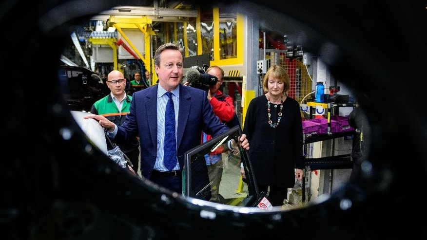 "Britain's Prime Minister David Cameron, centre, and  Labour Party, Member of Parliament Harriet Harman during their tour of the BMW Mini plant in Oxford England, while on a ""Remain"" EU referendum campaign visit Monday June 20, 2016. Britain goes to the polls in a referendum on Thursday on whether to leave or remain in the EU. (Leon Neal/PA via AP) UNITED KINGDOM OUT"