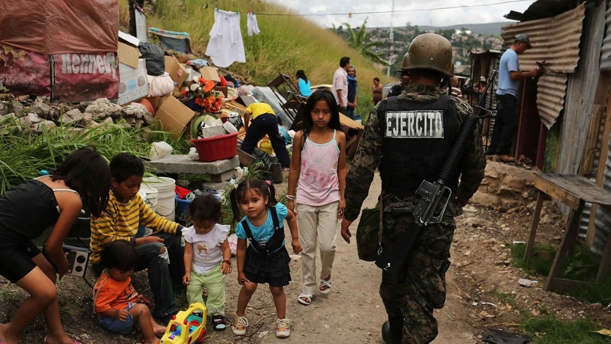 TEGUCIGALPA, HONDURAS - JULY 20:  Residents begin to dismantle their small shacks after being forced to vacate the community following a government ruling claiming  that the settlement was illegal on July 20, 2012 in Tegucigalpa, Honduras. Land disputes are becoming increasingly frequent in Honduras  which is alarming the nation's business class while sowing fears of increased political violence. In a nation where 72% of the poorest landowners hold only 11.6% of cultivated land, tensions are rising as the poor have few places to go and little opportunities for productive employment. Honduras now has the highest per capita murder rate in the world and its capital city, Tegucigalpa, is plagued by violence, poverty, homelessness and sexual assaults. With an estimated 80% of the cocaine entering the United States now being trans-shipped through Honduras, the violence on the streets is a spillover from the ramped rise in narco-trafficking.  (Photo by Spencer Platt/Getty Images)