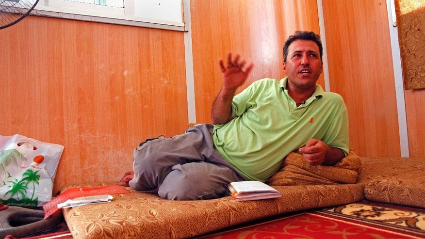 Salam Ashara, 43, recites one of his poems about pre-war Syria in his home in the Zaatari refugee camp,  northern Jordan, Sunday, June 19, 2016. Ashara and his family left Syria in early 2013, when no one expected the civil war there to rage for years, with no signs of relenting, and create the worst refugee crisis since World War II. The Asharas were one of the first families to settle in Zaatari. Ashara writes poetry to keep the memory of Syria alive in his six children, but says their future -- for now -- is in the camp, and that it will be years before they can return. (AP Photo/Sam McNeil)