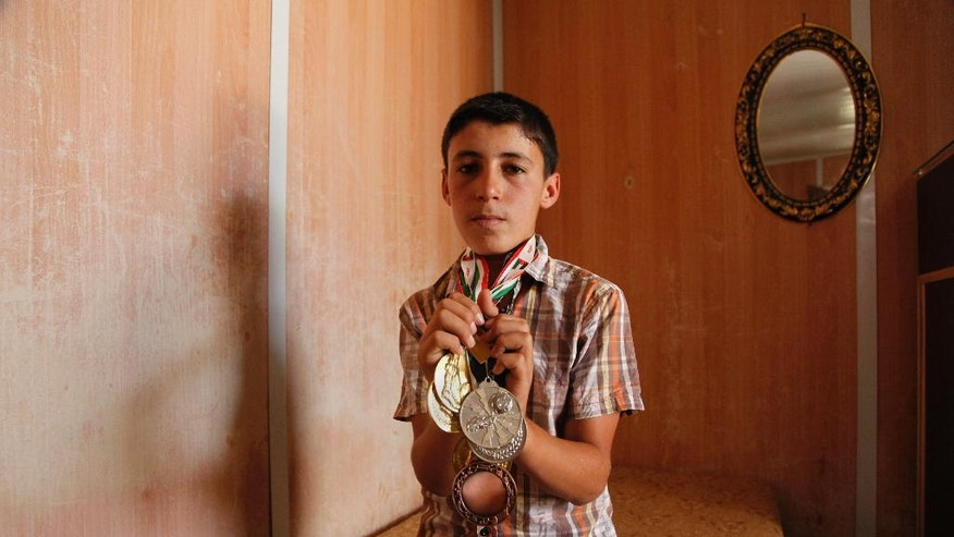 Ayman Ashara, 13, holds gold, silver and bronze medals he's earned playing football in the Zaatari refugee camp, northern Jordan, Sunday, June 19, 2016. His father Salam Ashara and his family left Syria in early 2013, when no one expected the civil war there to rage for years, with no signs of relenting, and create the worst refugee crisis since World War II. The Asharas were one of the first families to settle in Zaatari. Ashara writes poetry to keep the memory of Syria alive in his six children, but says their future -- for now -- is in the camp, and that it will be years before they can return.  (AP Photo/Sam McNeil)