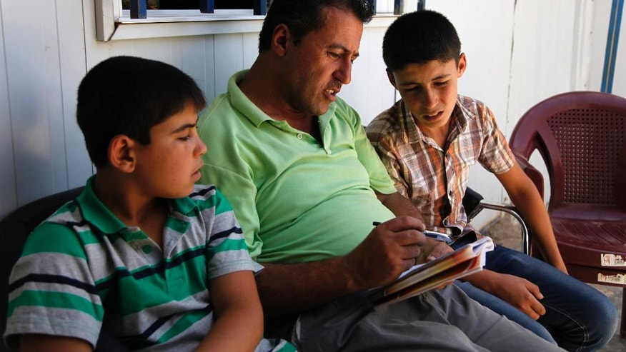 Salam Ashara, center, reads his poems about pre-war Syria to his two sons Saeb, left, and Ayman in the Zaatari refugee camp, northern Jordan, Sunday, June 19, 2016. Ashara and his family left Syria in early 2013, when no one expected the civil war there to rage for years, with no signs of relenting, and create the worst refugee crisis since World War II. The Asharas were one of the first families to settle in Zaatari. Ashara writes poetry to keep the memory of Syria alive in his six children, but says their future -- for now -- is in the camp, and that it will be years before they can return.  (AP Photo/Sam McNeil)