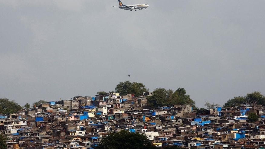 FILE- In this June 15, 2016 file photo, an aircraft of India's private airline Jet Airways flies above shanties adjacent to the Chhatrapati Shivaji airport as it prepares to land in Mumbai, India. India has announced radical changes in its foreign direct investment rules to attract overseas investment into its aviation and defense industries.Defense and airlines industries can now be 100 percent foreign owned, after previous rules allowed 74 percent and 49 percent, respectively. (AP Photo/ Rajanish Kakade, File)