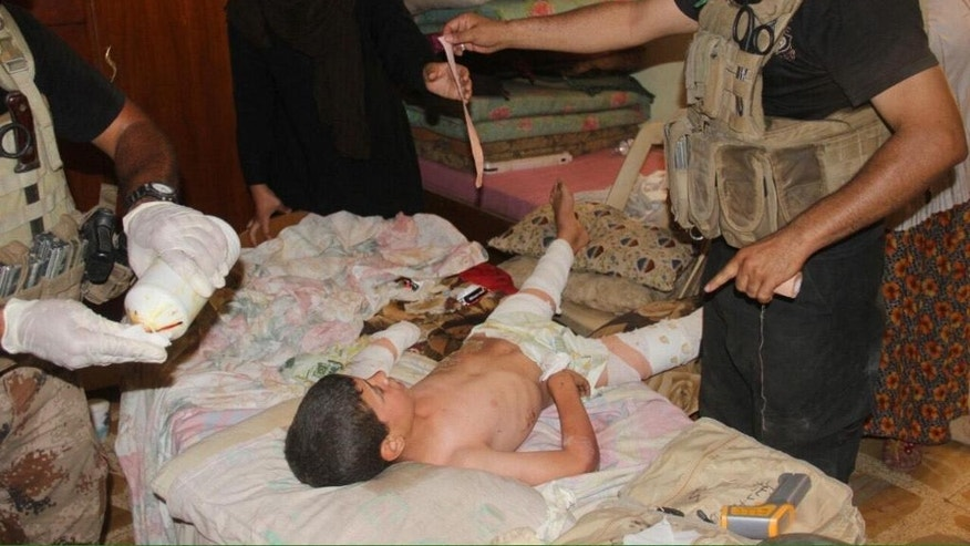 In this image taken by an Iraqi Counterterrorism Service photographer on Sunday, June 19, 2016, medics treat a boy who escaped Islamic State militants in Fallujah, Iraq. Thousands of civilians are fleeing Fallujah after the city was declared liberated from the Islamic State group, the United Nations said, while an Iraqi commander reported fierce clashes as elite counterterrorism forces pushed to clear out the remaining militants.(Iraq Counterterrorism Service via AP)