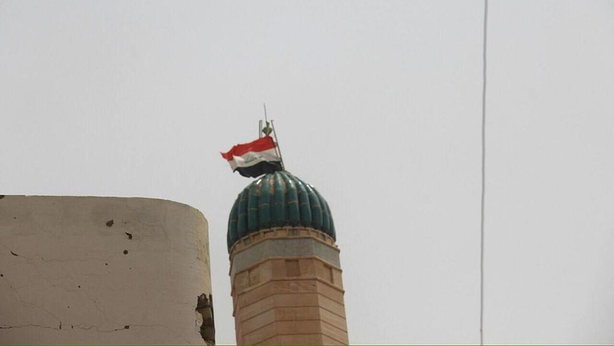 In this image taken by an Iraqi Counterterrorism Service photographer on Sunday, June 19, 2016, the national flag flies over a minaret in Fallujah, Iraq after forces re-took the city center after two years of Islamic State control. Thousands of civilians are fleeing Fallujah after the city was declared liberated from the Islamic State group, the United Nations said, while an Iraqi commander reported fierce clashes as elite counterterrorism forces pushed to clear out the remaining militants. (Iraq Counterterrorism Service via AP)