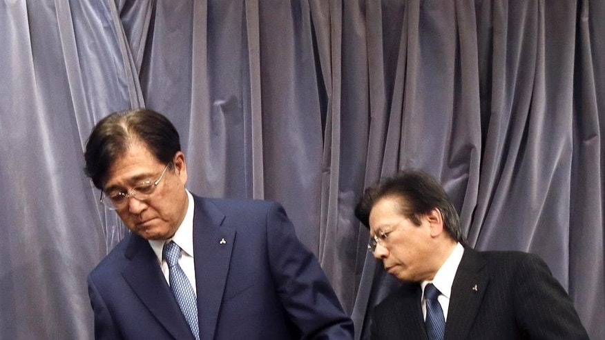 In this May 11, 2016 photo, Mitsubishi Motors Corp. Chairman and CEO Osamu Masuko, left, and President Tetsuro Aikawa prepare for their press conference in Tokyo. The Japanese government said Tuesday, June 21, 2016 that Mitsubishi Motors Corp. overstated mileage on its vehicles by up to 16 percent, but stopped short of slapping further penalties on the company. (AP Photo/Eugene Hoshiko)