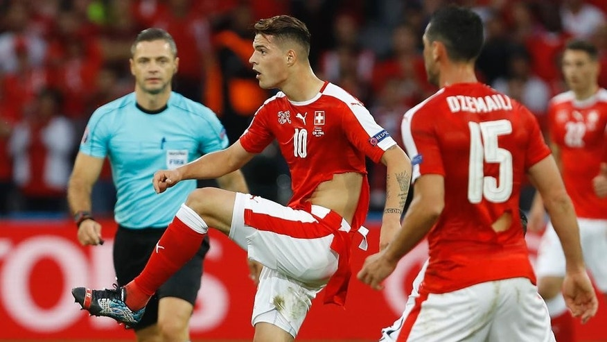 Switzerland's Blerim Dzemaili, right, and Granit Xhaka play with ripped jerseys during the Euro 2016 Group A soccer match between Switzerland and France at the Pierre Mauroy stadium in Villeneuve d'Ascq, near Lille, France, Sunday, June 19, 2016. (AP Photo/Darko Vojinovic)