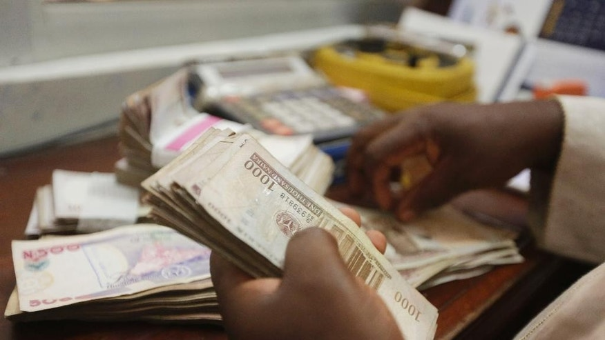FILE- In this file photo taken Tuesday, Oct. 20, 2015, a money changer counts Nigerian Naira currency at a bureau de change in Lagos, Nigeria. Nigeria's currency plummeted Monday, June 20, 2016, losing more than a third of its value as the government floated the Naira for the first time in the history of the oil-producing nation. (AP Photo/Sunday Alamba,File)