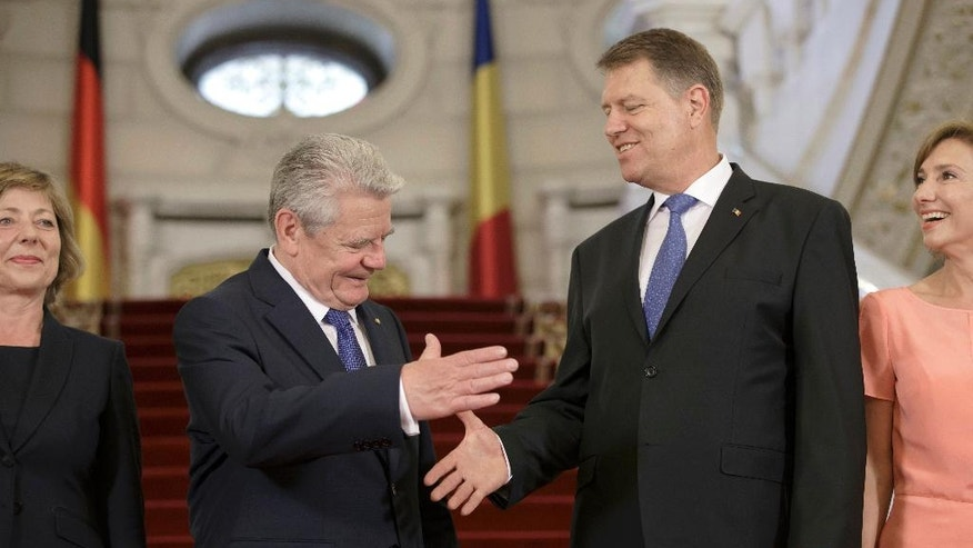 German President Joachim Gauck, left, shakes hands with his Romanian counterpart Klaus Iohannis as his partner Daniela Schadt, left, and Carmen Ioannis smile during the official welcoming ceremony at the Cotroceni Presidential Palace in Bucharest, Romania, Monday, June 20, 2016. Joachim Gauck and his partner Daniela Schadt is on a state visit to Romania. (AP Photo/Vadim Ghirda)