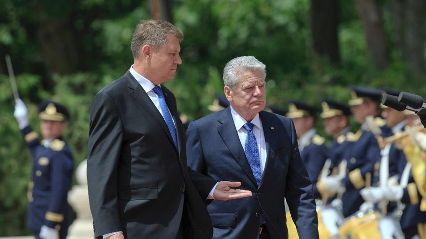 German President Joachim Gauck, right, reviews an honor guard with his Romanian counterpart Klaus Iohannis during the official welcoming ceremony at the Cotroceni Presidential Palace in Bucharest, Romania, Monday, June 20, 2016. Joachim Gauck and his partner Daniela Schadt is on a state visit to Romania. (AP Photo/Vadim Ghirda)