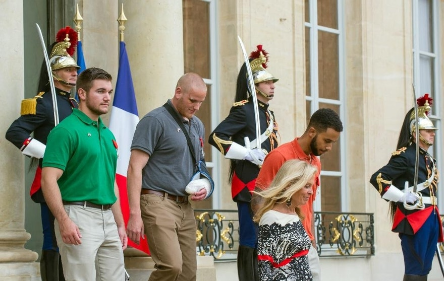 CORRECTS SADLER'S SCHOOL TO SACRAMENTO STATE UNIVERSITY, INSTEAD OF SACRAMENTO UNIVERSITY - U.S. National Guardsman from Roseburg, Ore., Alek Skarlatos,  left, U.S. Airman Spencer Stone, second left, and Anthony Sadler, right, a senior at Sacramento State University in California, leave the Elysee Palace in Paris, France, with U.S. Ambassador to France Jane D. Hartley after being awarded the French Legion of Honor by French President Francois Hollande on Monday, Aug. 24, 2015. The three American travelers say they relied on gut instinct and a close bond forged over years of friendship as they took down a heavily armed man on a passenger train speeding through Belgium on Friday, Aug. 21. (AP Photo/Kamil Zihnioglu)