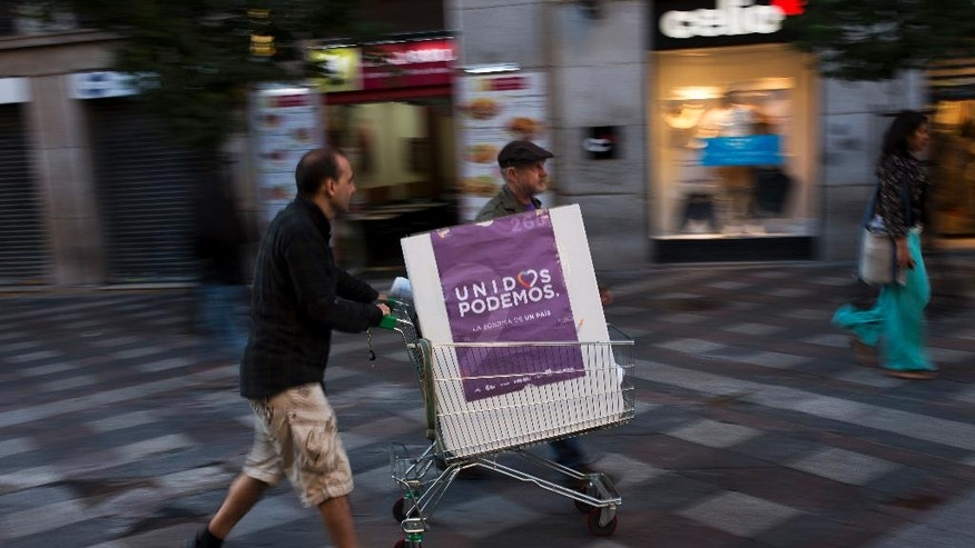 In this Wednesday, June 15, 2016 photo, volunteers of the Spain's Unidos Podemos coalition party pull a trolley with a poster of the party after being handing out flyers in Madrid, Spain. After heading six governments and dominating the left for nearly four decades, Spain's Socialist party faces an unprecedented risk of being overtaken by an upstart far left alliance during the country's June 26 repeat election. It's a development that would upend the nation's political landscape for the second time in just six months. (AP Photo/Francisco Seco)