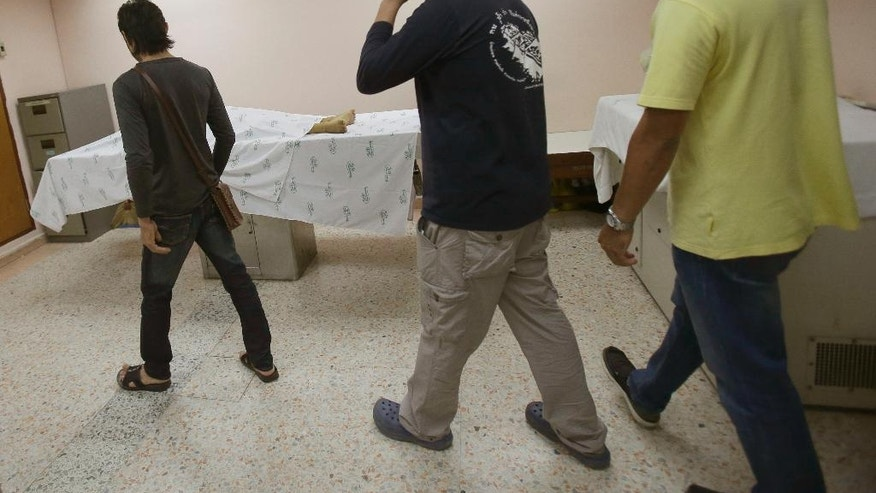 Three men convicted of drunk drinking are led into a morgue at Taksin Hospital in Bangkok, Thailand, Monday, June 20, 2016.  A group of convicted drunken drivers were brought to a Bangkok morgue Monday to see a corpse and reflect on the gory consequences of their actions as part of a program aimed at combating the carnage on Thailand's roads. (AP Photo/Sakchai Lalit)