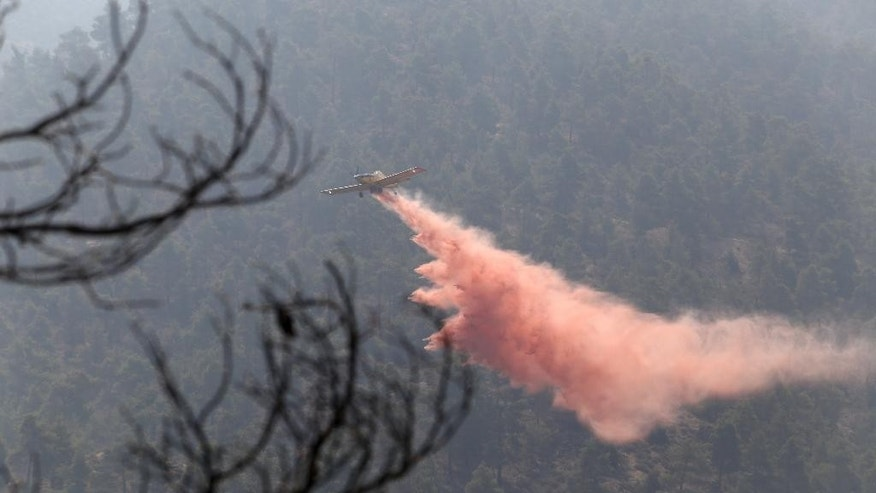 A firefighting aircraft drops fire retardant material in efforts to contain a huge forest fire that continues to rage out of control for a third day in the mountainous areas southwest of Cyprus' capital Nicosia Tuesday, June 21, 2016. The fire has claimed the lives of two fire fighters. More planes from Italy and France are expected later Tuesday to join 16 other aircraft from Greece, Israel, Cyprus and British forces stationed on two military bases on the east Mediterranean island in battling the fire. (AP Photo/Philippos Christou )