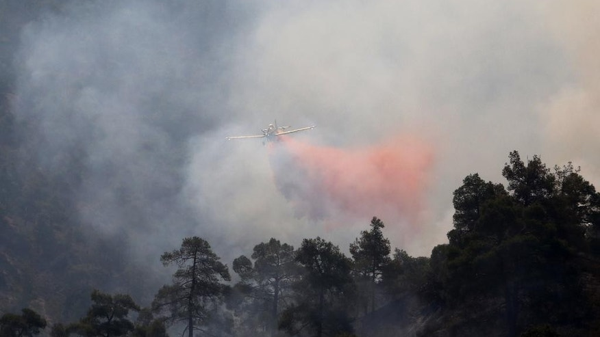 A firefighting aircraft drops fire retardant material in efforts to contain a huge forest fire that continues to rage out of control for a third day, in the mountainous areas southwest of Cyprus' capital Nicosia, Tuesday, June 21, 2016. The fire has claimed the lives of two fire fighters. More planes from Italy and France are expected later Tuesday to join 16 other aircraft from Greece, Israel, Cyprus and British forces stationed on two military bases on the east Mediterranean island in battling the fire. (AP Photo/Philippos Christou )