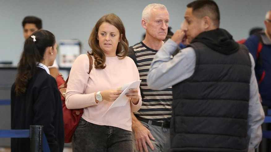 Melissa Reid, of Britain, center, walks next to her father William Reid, second right, before boarding a flight in Lima, Peru, Tuesday, June 21, 2016. Reid who was deported from Peru, along with Irish-born Michaella McCollum, was detained on Aug. 6, 2013, at Lima's airport for allegedly trying to smuggle cocaine on a flight to Spain. (AP Photo/Martin Mejia)